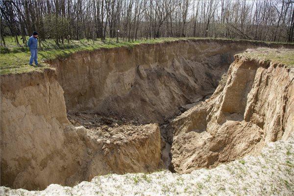 A gödör feltehetően egy földalatti vízmosás miatt keletkezett a sok földmunkától fellazult földben. A területet életveszély miatt lezárták. Fotó: Varga György (MTI)